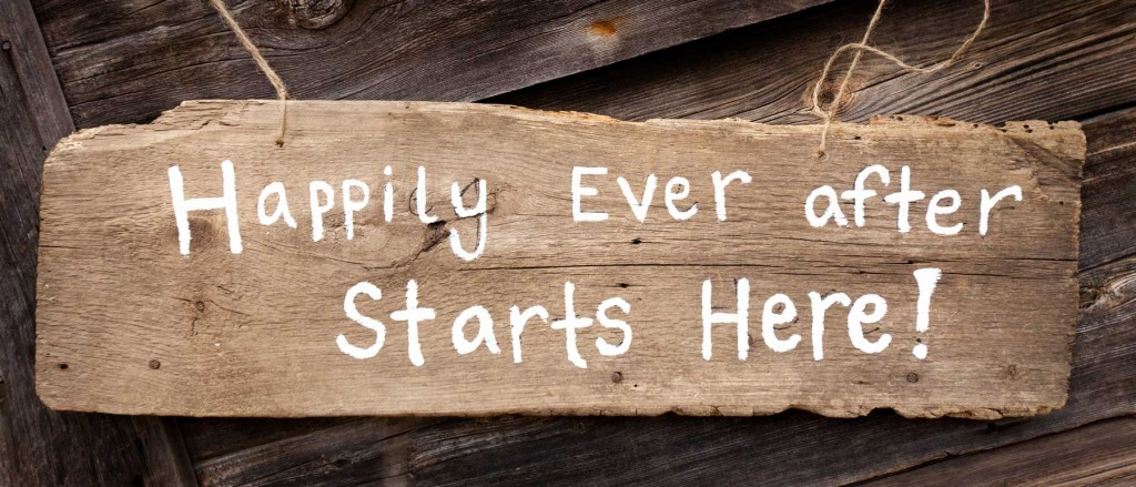 cute handmade wooden wedding sign against old building saying happily ever after starts here