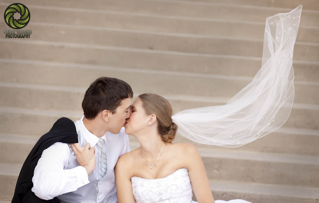 bride and groom kissing on stairway with blowing veil in wind - wedding photo gallery